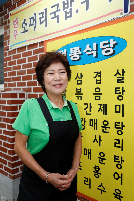 SK서민지원 대출 1만번째 수혜자인 윤복임씨가 서울 성북구 정릉에 위치한 자기 가게 앞에서 포즈를 취하고 있다