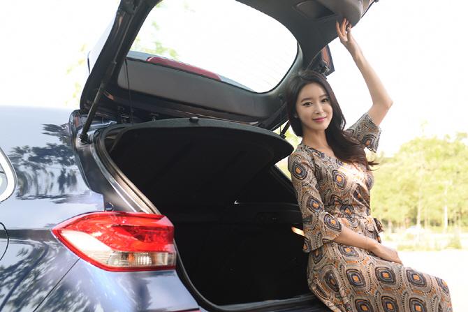 i30의 트렁크에 앉아 카메라를 쳐다보는 레이싱 모델 소이