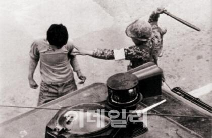 """시민을 몽둥이로 때리려고 하는 계엄군. 전두환 전 대통령은 """"대한민국 국군이 국민을 상대로 잔인무도한 살인행위를 했다는 것을 상상조차 할 수 없다""""며 무력진압 사실을 부정했다(사진=5·18기념재단)."""