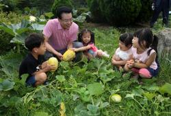 [포토] 어린이와 참외 수확하는 성장현 용산구청장